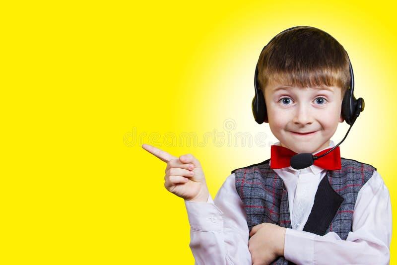 Усмехаясь мальчик указывая вверх на космос экземпляра с headse телефона стоковая фотография