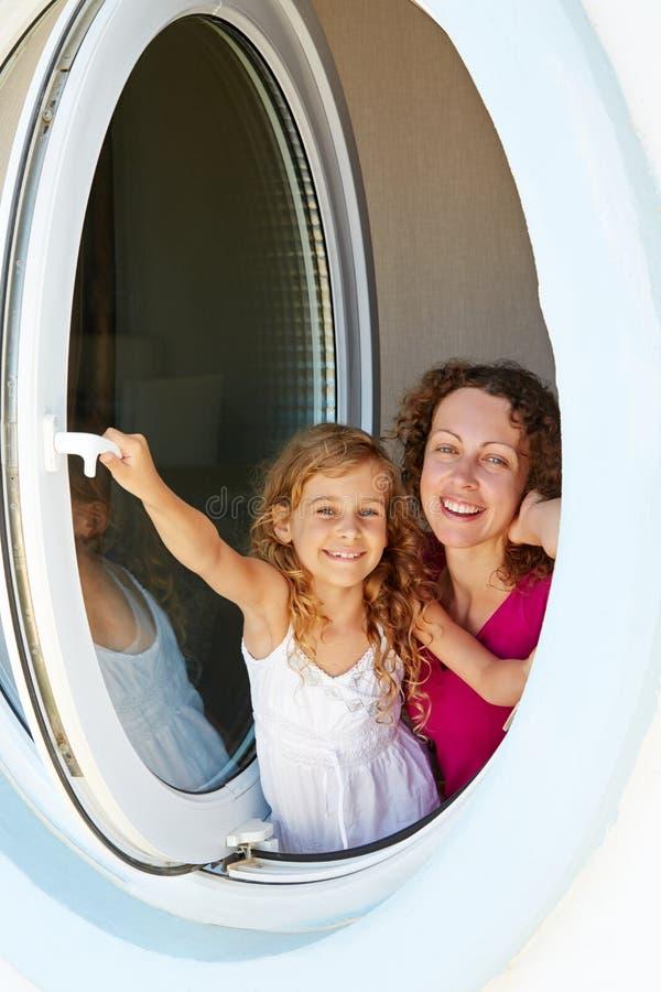 Усмехаясь мать и ее взгляд дочери вне от окна стоковое фото rf