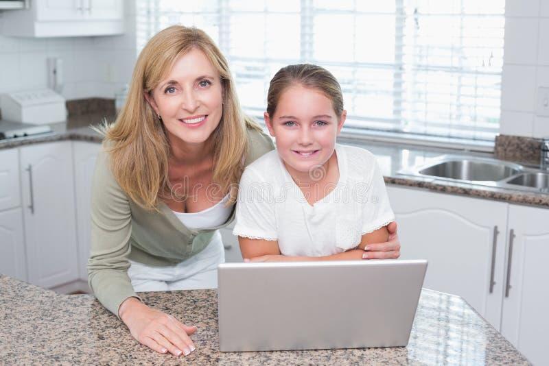 Усмехаясь мать и дочь используя компьтер-книжку совместно стоковое фото