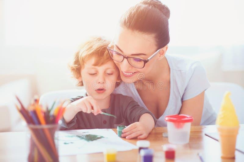 Усмехаясь мать уча, что ее сын нарисовал стоковое фото rf