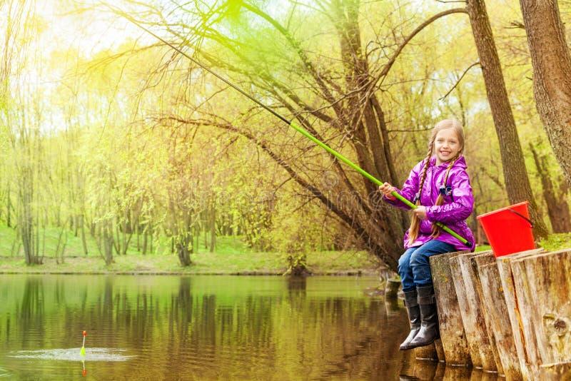 Усмехаясь малая девушка удя около красивого пруда стоковая фотография rf