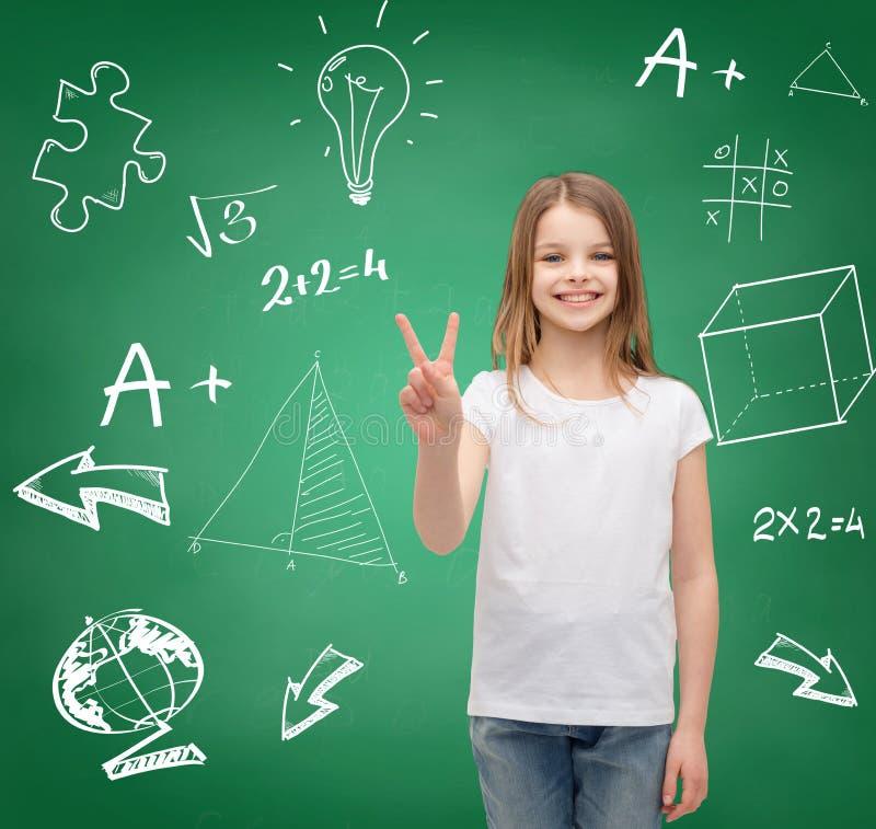 Усмехаясь маленькая девочка в белом показывая знаке победы стоковая фотография rf
