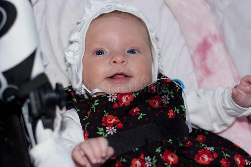 Усмехаясь маленькая девочка в крышке и мантии стоковые фотографии rf