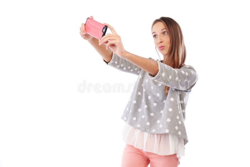 Усмехаясь маленькая девочка делая фото selfie и puckering губы на стоковое изображение rf