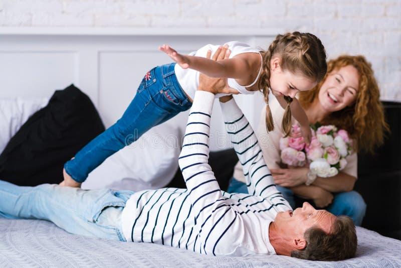 Усмехаясь маленькая девочка играя игры с ее дедом стоковое фото