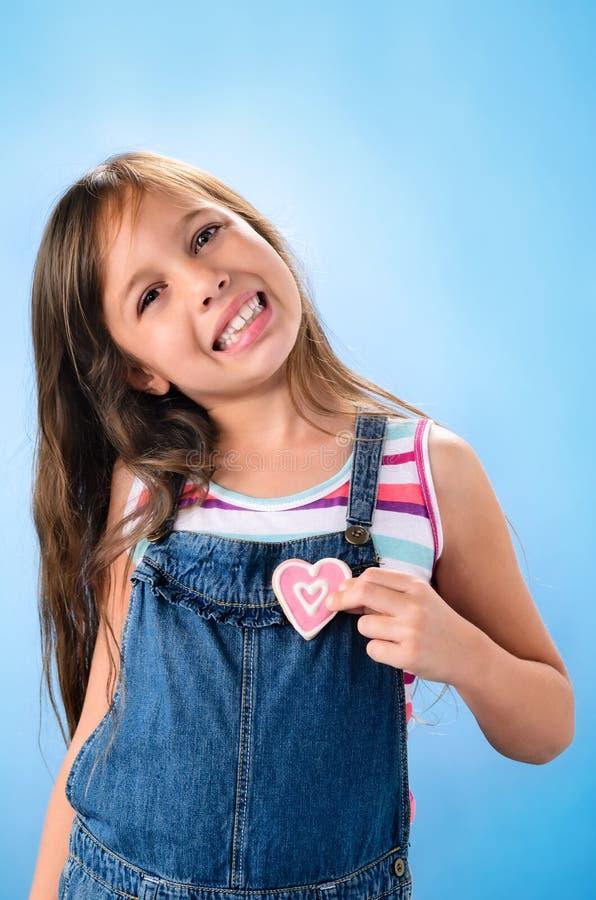 Усмехаясь маленькая девочка кладет печенья к сердцу стоковые фотографии rf