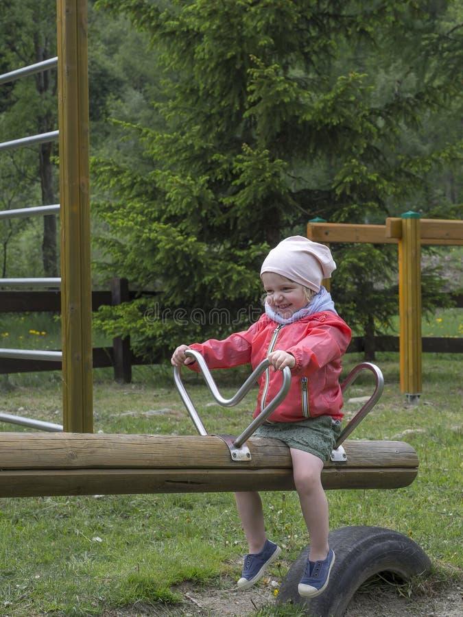 Усмехаясь маленькая девочка на качании спортивной площадки стоковая фотография