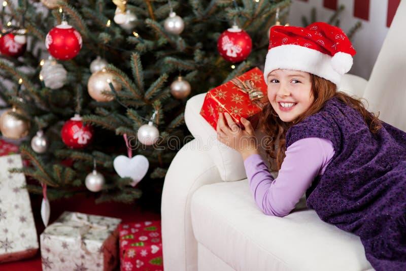 Усмехаясь маленькая девочка перед рождественской елкой стоковое фото rf