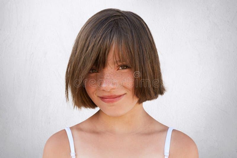 Усмехаясь маленькая девочка при стильный hairdo, темные глаза и freckled сторона представляя против белой предпосылки Милая девуш стоковые изображения rf