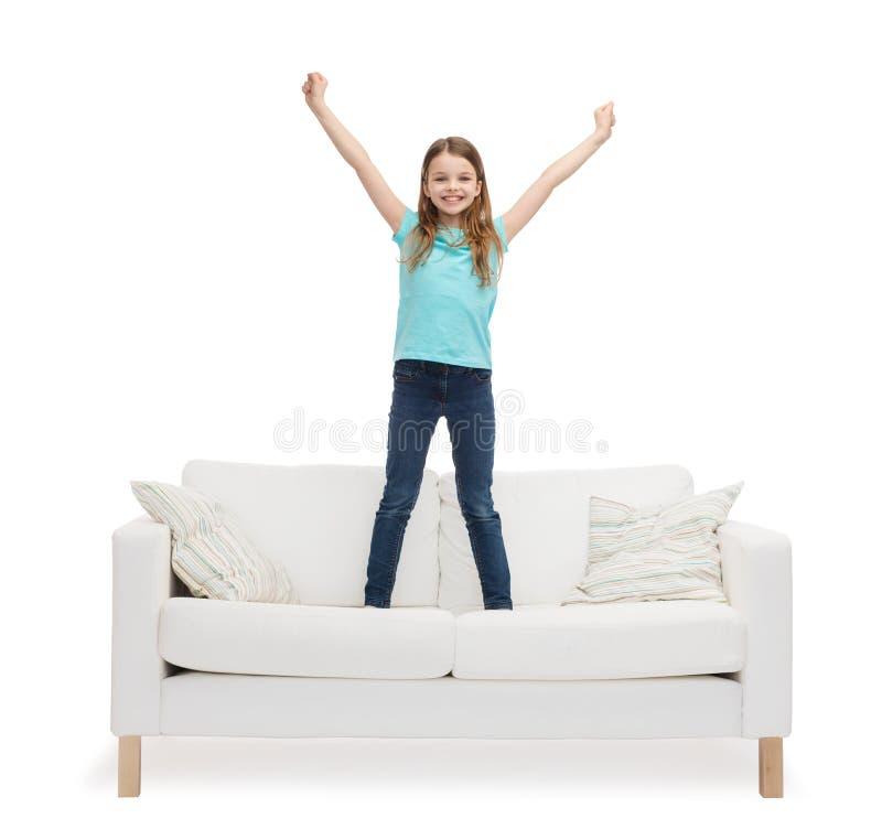 Усмехаясь маленькая девочка скача или танцуя на софе стоковая фотография