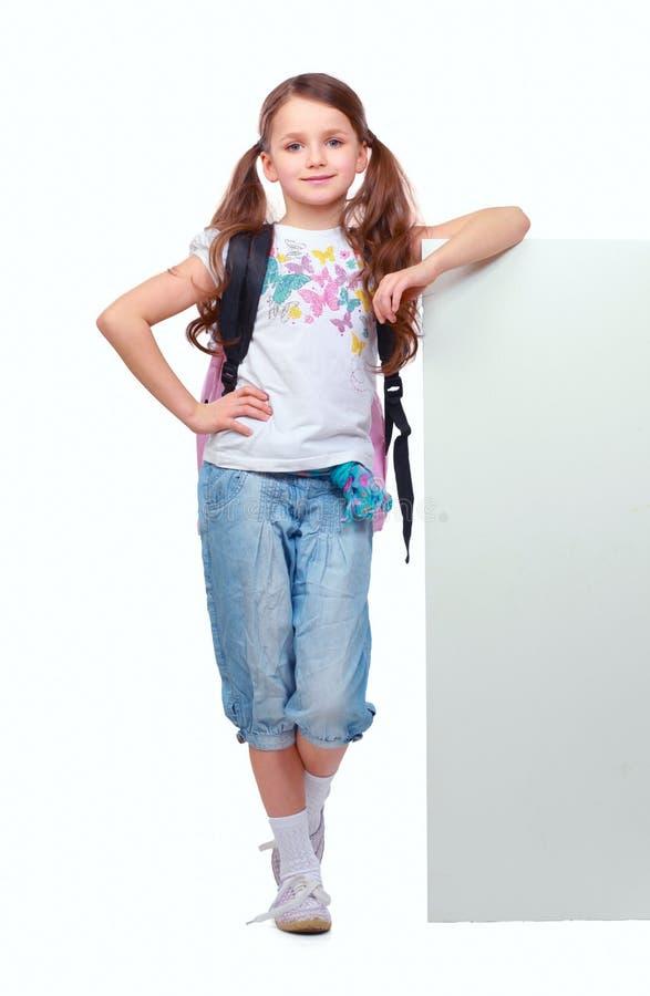 Усмехаясь маленькая девочка стоя около пустой белой доски стоковое изображение
