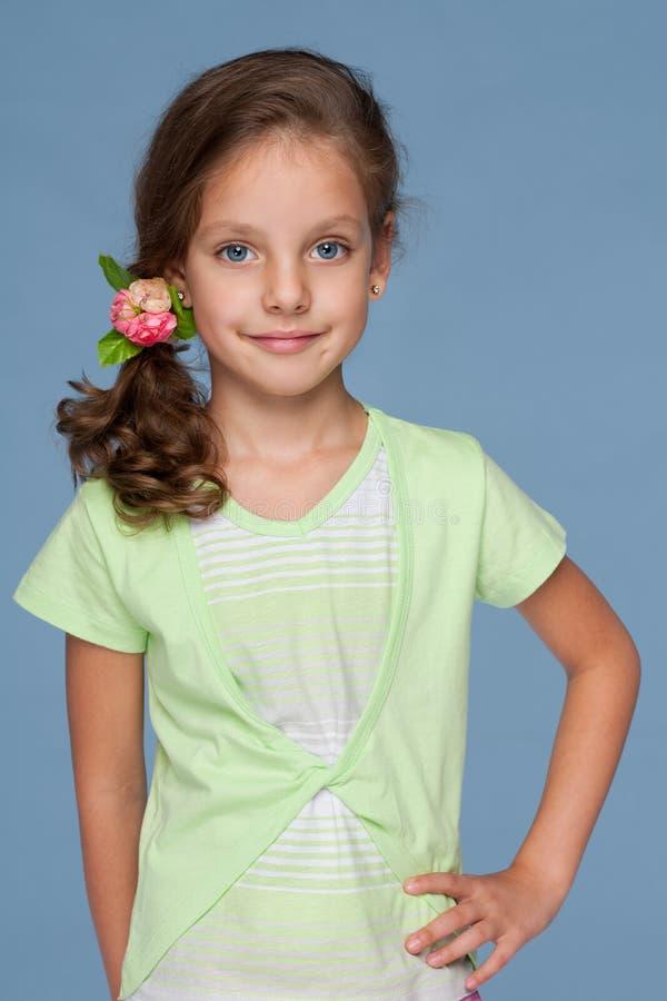 Усмехаясь маленькая девочка с красивым стилем причёсок стоковое фото