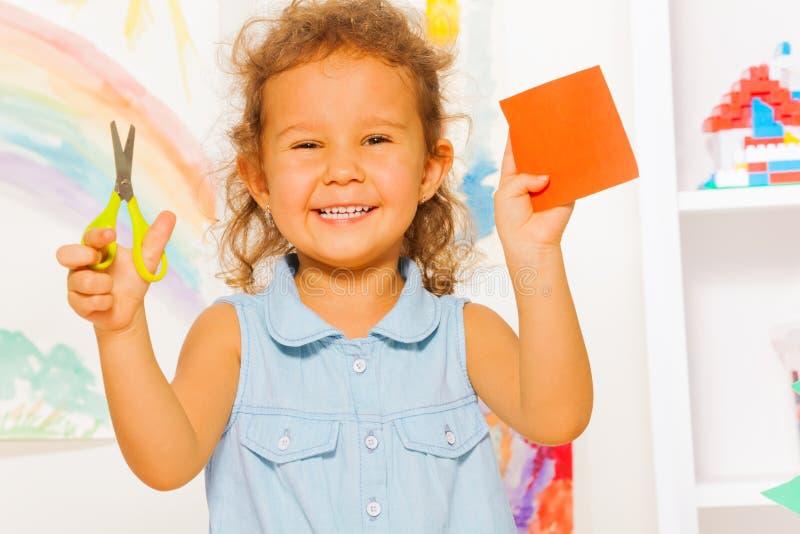 Усмехаясь маленькая девочка с ножницами и квадратом стоковые фотографии rf