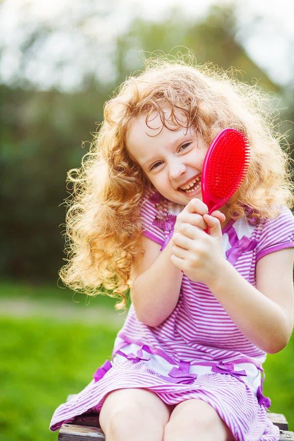 Усмехаясь маленькая девочка чистя ее волосы щеткой стоковые изображения
