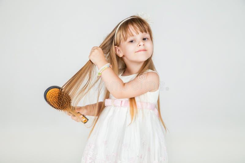 Усмехаясь маленькая девочка чистя ее крупный план щеткой волос стоковое изображение