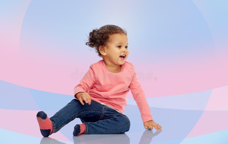Усмехаясь маленький ребёнок сидя на поле стоковые фотографии rf