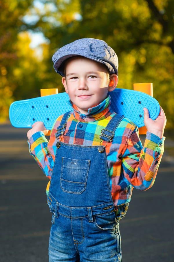 Усмехаясь мальчик держа доску пенни цвета пластичную стоковое фото