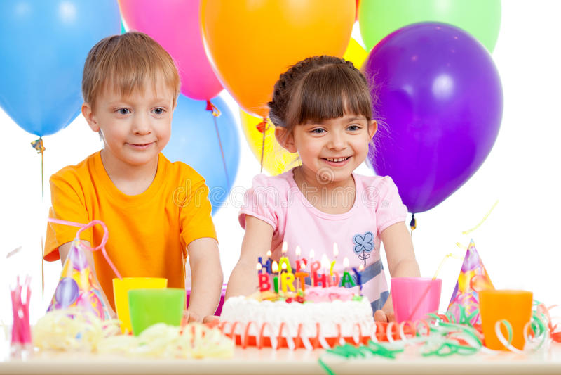 Усмехаясь мальчик и девушка с именниным пирогом и баллонами цвета стоковое изображение