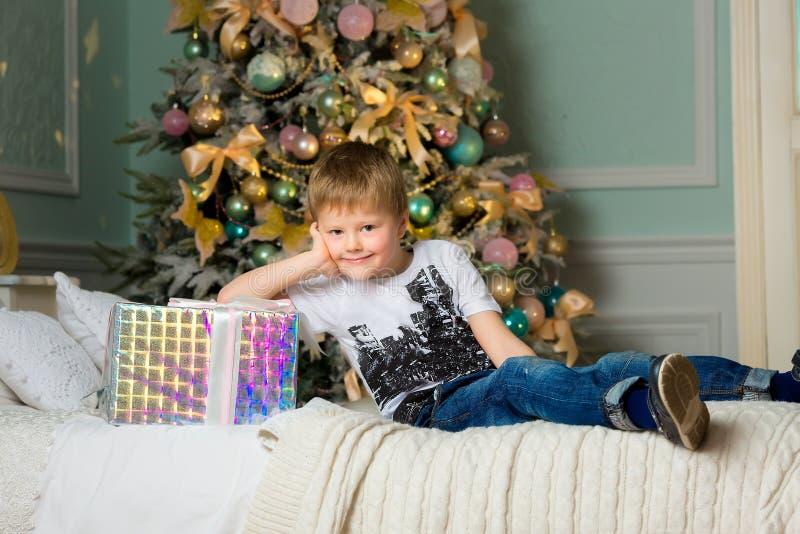 Усмехаясь мальчик обнимая конец коробки Новый Год стоковые изображения