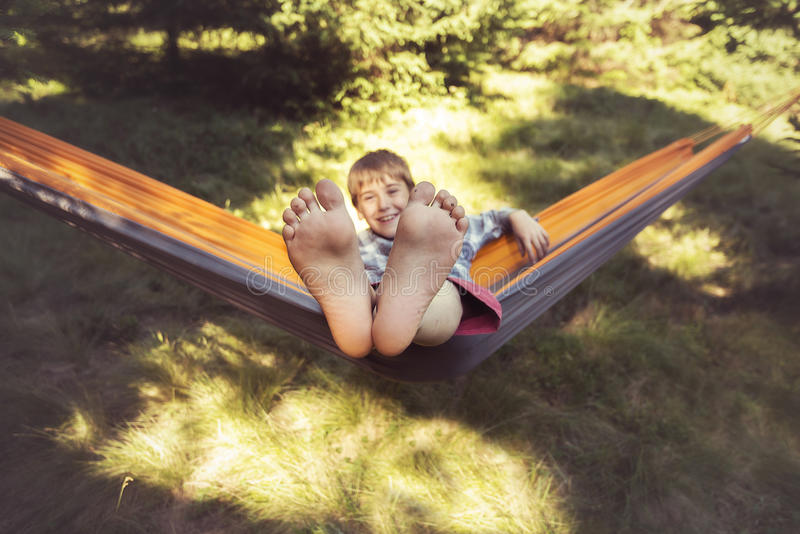 Усмехаясь мальчик отбрасывает в гамаке Его ноги близкие поднимающие вверх стоковые фотографии rf