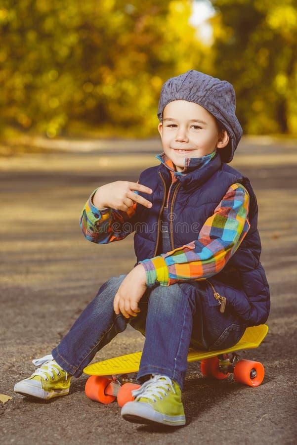 Усмехаясь мальчик сидя на пенни цвета пластичном всходит на борт стоковая фотография rf