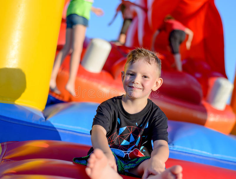 Усмехаясь мальчик сидя на скача замке стоковое фото rf