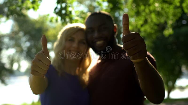 Усмехаясь межрасовые пары показывая большие пальцы руки вверх и смотреть камеру, отношение стоковое изображение