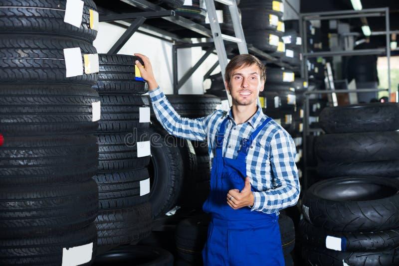 Усмехаясь механик укомплектовывает личным составом работу с автошинами автомобиля в мастерской стоковые изображения rf