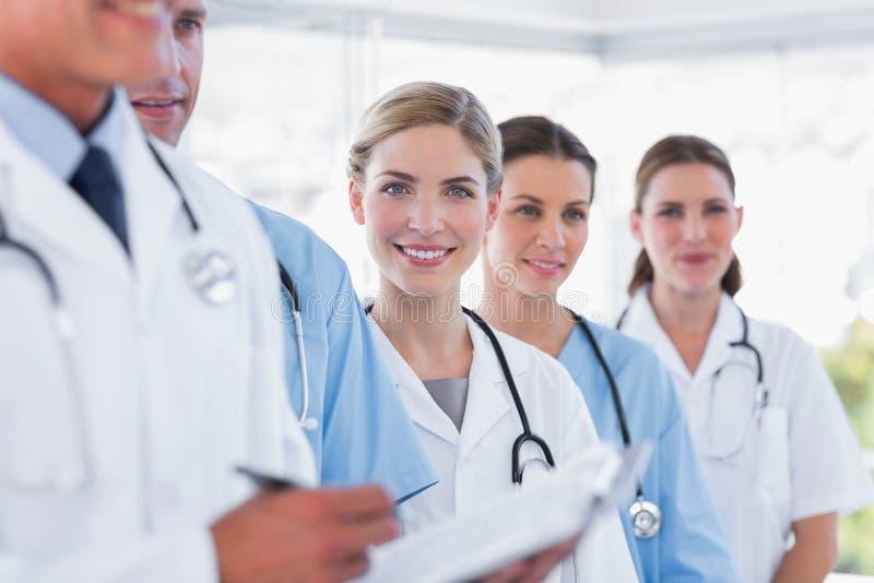 Усмехаясь медицинская бригада в строке стоковые изображения rf