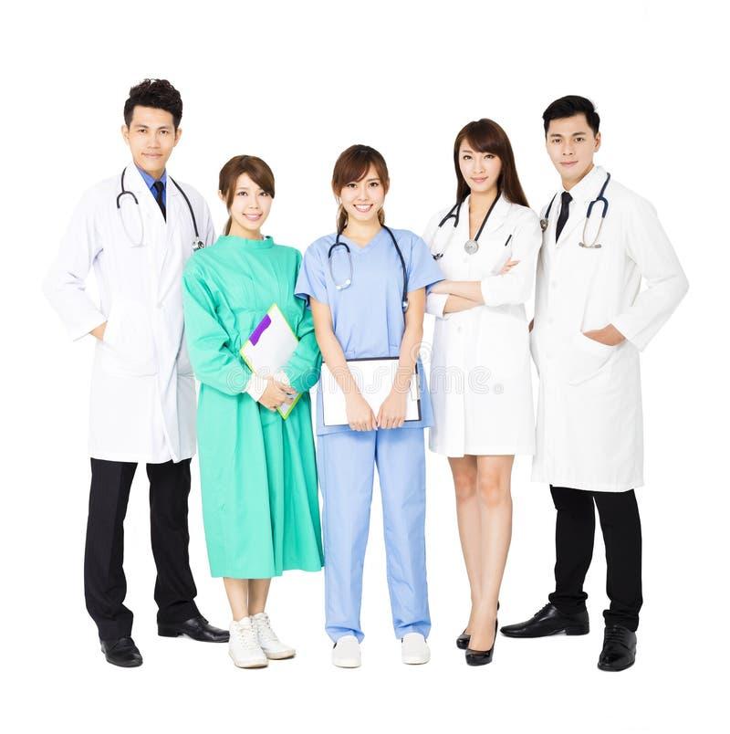 Усмехаясь медицинская бригада стоя совместно изолированный на белизне стоковые фотографии rf