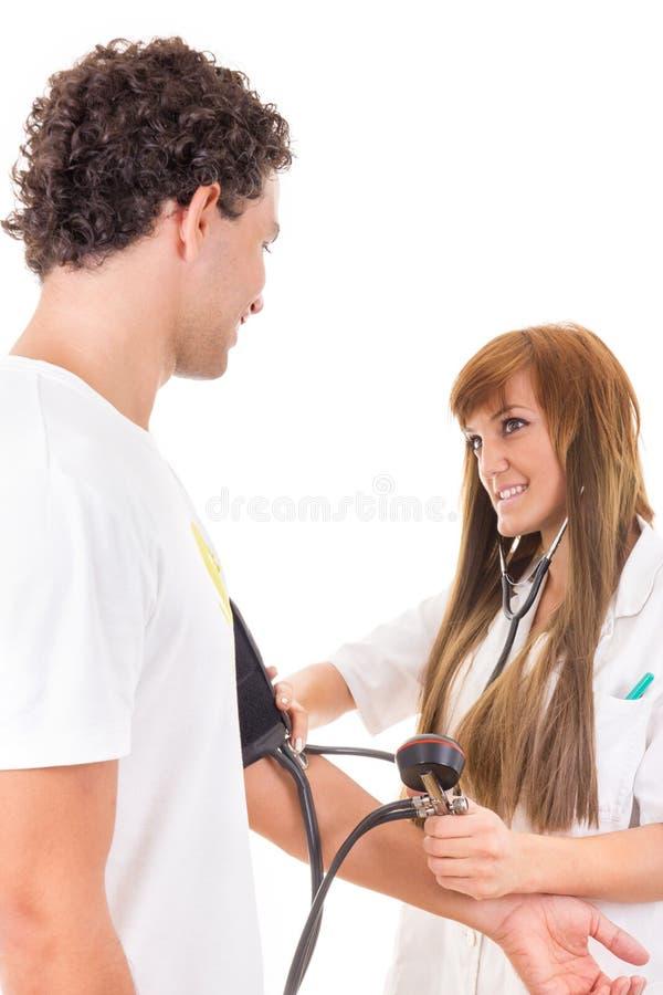 Усмехаясь медсестра или доктор измеряют кровяное давление satisfi стоковое фото rf