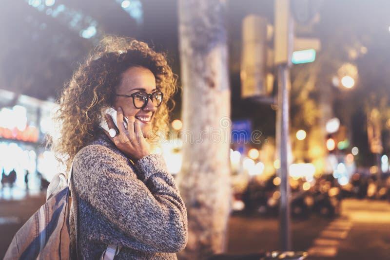 Усмехаясь милая женщина делая переговор вызывает с ее друзьями через телефон клетки пока стоящ на ноче на улице стоковое фото rf