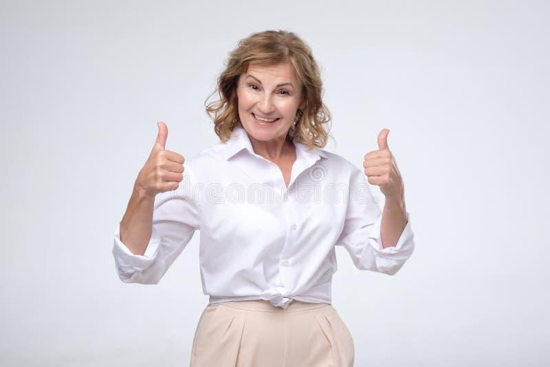 Усмехаясь милая зрелая женщина показывая большие пальцы руки вверх стоковое изображение