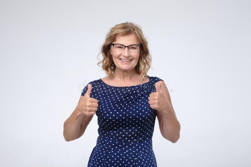 Усмехаясь милая зрелая женщина показывая большие пальцы руки вверх стоковое фото
