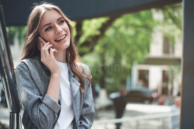 Усмехаясь милая молодая женщина говоря на smartphone стоковое изображение