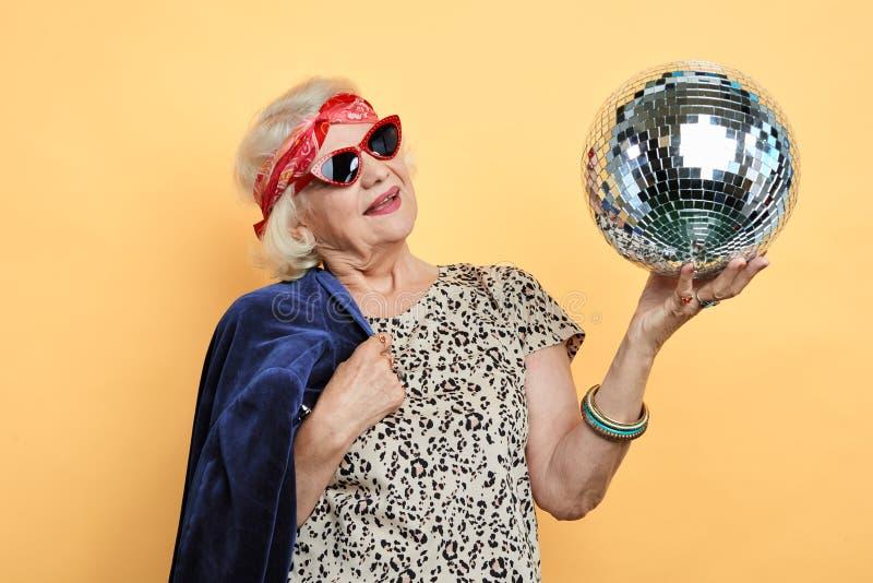 Усмехаясь милая старуха смотря шарик стоковые изображения