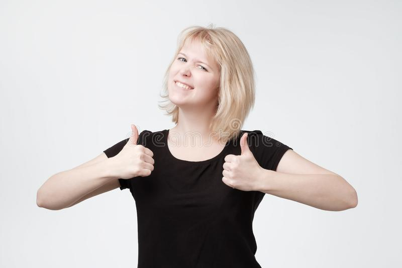 Усмехаясь милый молодой белокурый подросток показывая большие пальцы руки вверх стоковое изображение