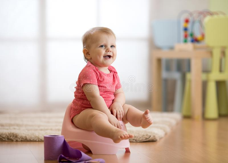 Усмехаясь младенец сидя на ночном горшке с креном туалетной бумаги стоковое фото
