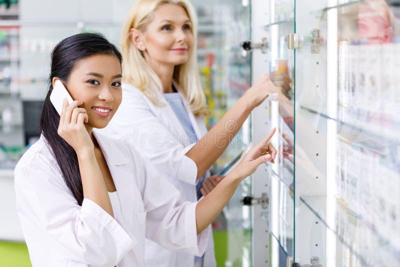 усмехаясь многонациональные женские аптекари работая совместно стоковые изображения rf