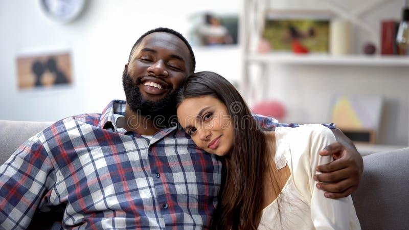 Усмехаясь многонациональные пары обнимая на софе, ослабляя совместно, нежные чувства стоковое фото rf