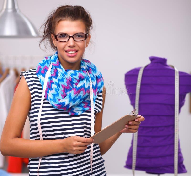 Усмехаясь модельер стоя близко манекен в офисе стоковое изображение