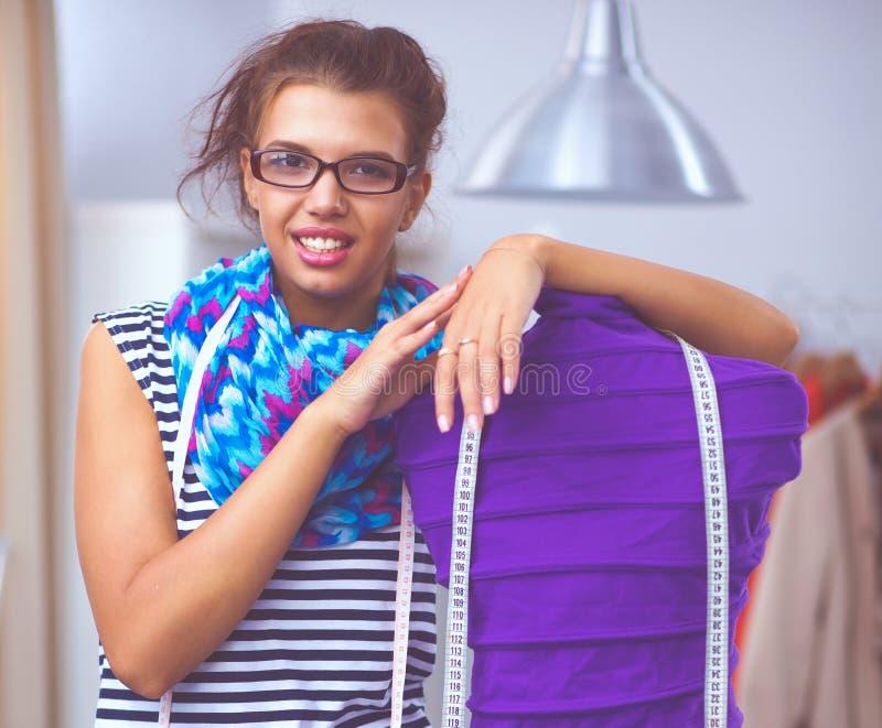 Усмехаясь модельер стоя близко манекен в офисе стоковые изображения rf