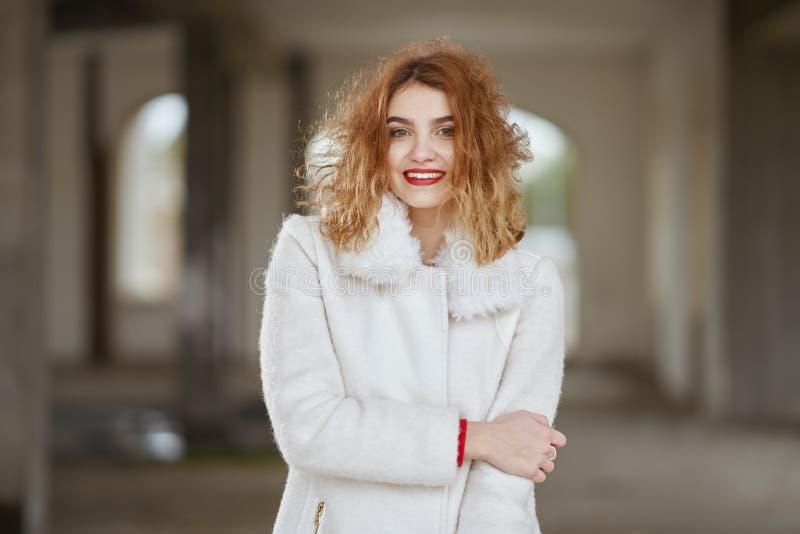 Усмехаясь модная рыжеволосая девушка с волосами летания в белом пальто представляя в большой комнате стоковое изображение