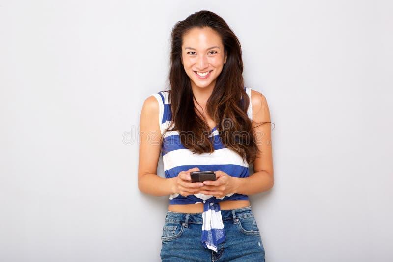 Усмехаясь молодая азиатская женщина держа мобильный телефон стоковые изображения