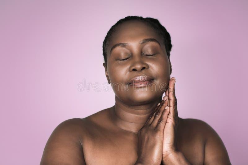 Усмехаясь молодая африканская женщина стоя с ее глазами закрыла стоковые фотографии rf