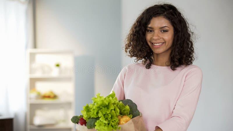 Усмехаясь молодая дама с продуктовой сумкой, здоровьем и красотой, органическим питанием, едой стоковое фото rf