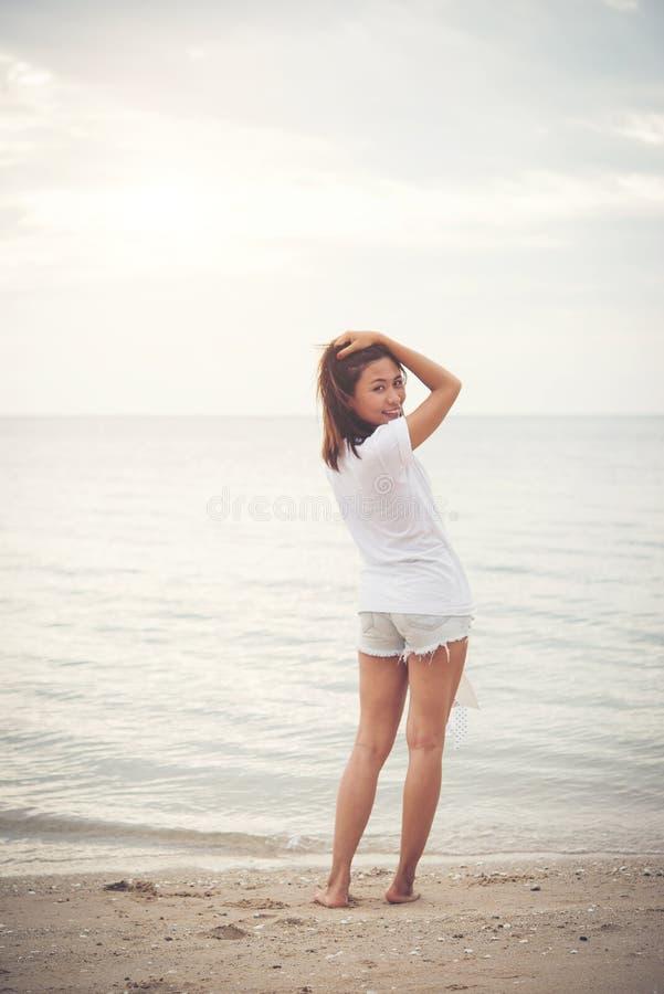Усмехаясь молодая женщина в белой футболке стоя на пляже стоковые фотографии rf