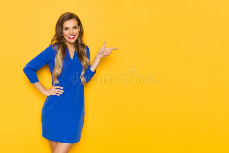 Усмехаясь молодая женщина в голубом платье указывающ и смотрящ камера стоковая фотография rf