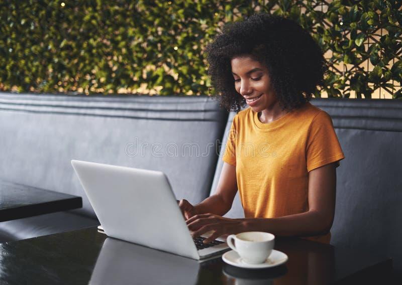 Усмехаясь молодая женщина в кафе печатая на ноутбуке стоковая фотография rf