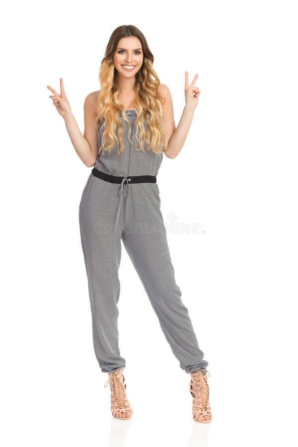 Усмехаясь молодая женщина в комбинезоне показывает знак руки мира стоковые изображения